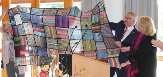 Bürgermeister Thomsen präsentiert die Patchwork-Decke, die von neuen und alten Stuhrer Bürgern gestrickt wurde.