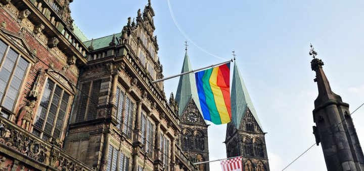 Die Fotomontage zeigt, wie das Rathaus mit Regenbogenflagge aussehen würde. Montage: Schlie