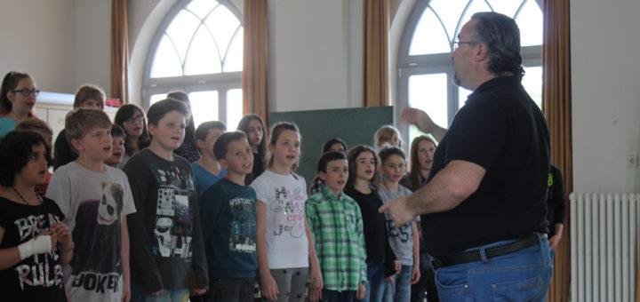 """Verstehen sich schon während der Proben bestens: Die Kinder von """"ThinkMusic!"""" und Juilo Fernández (r.) von der Hochschule Bremen. Foto: Waalkes"""