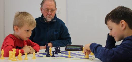 Leon und Filipp (v.l., beide sechs Jahre alt) spielen Schach wie zwei ganz Große. Wilfried Buchterkirche (m.) bietet zweimal wöchentlich ehrenamtlich die Schachgruppe in der KiTa Flintacker an. Foto: Füller