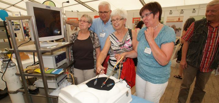 """Chefarzt Dr. Michael Spatny vom Kreiskrankenhaus Osterholz ließ Besucherinnen an einem Modell Eingriffe """"durchs Schlüsselloch"""", die so genannte Endoskopie, probieren. Foto: Möller"""