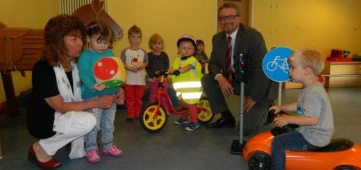 Kita-Leiterin Christel Gödeke (l.) freute sich mit den Kindern über Warnwesten und ein Laufrad, das ihnen Landrat Bernd Lütjen am Freitag überbrachte. Foto: Bosse