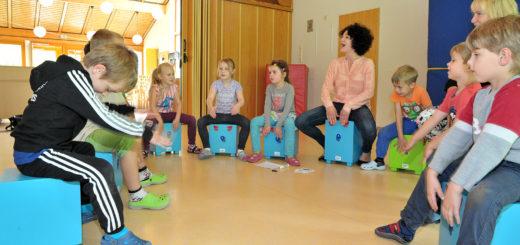 Alle 123 Kinder aus den sechs Gruppen in der Kita Schatzinsel haben am Montag die Trommelhocker kennengelernt. Anne Higgen (Mitte) sorgte für die ersten wohlklingenden Töne. Foto: Konczak