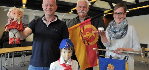 """Jürgen Lüdtke (Mitte) zeigt ein Teil seiner DDR-Exponate zum Thema """"Kindheit und Jugend in der DDR"""" im Huder Rathaus. (Links im Bild: Wirtschaftsförderer Roland Arndt; rechts Gemeindemitarbeiterin Regina Wolff.Foto: Konczak"""
