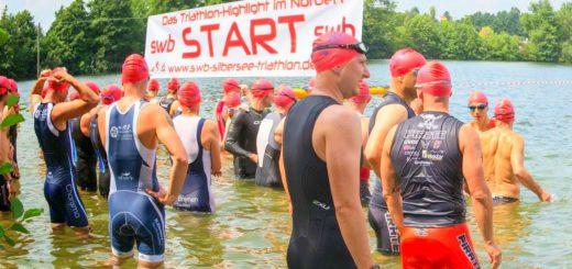 Die Schwimmer vor dem Start des Silbersee-Triathlons im Silbersee in Stuhr. Nach dem Schwimmen müssen die Teilnehmer auch noch Fahrrad fahren und laufen. Sponsoren sind unter anderem swb, Vilsa und der Türenheld.