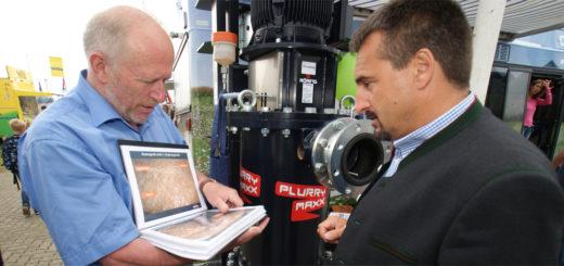 Der dreifache Rodel-Olympiasieger Georg Hackl (r.) lässt sich am Stand des Fachverbandes Biogas von Wilhelm Gantefort einen Nasszerkleinerer vorführen. Foto: Möller