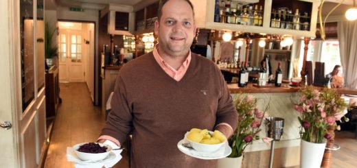 """Wirt Rainer Sheikh unterhält im """"Herman' Post"""" die Gäste mit flotten Sprüchen und leckerem Essen – wie dem Rinderbraten mit Rotkohl. Foto: Schlie"""