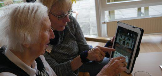 Die Betreuerin zeigt einer Seniorin auf dem Tablet ihre Heimat. Foto: Caritas