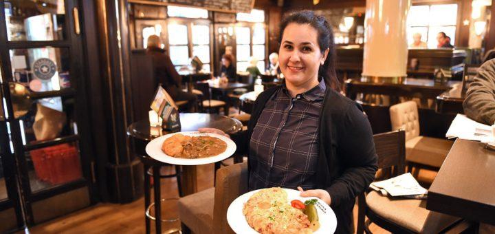 """Wirtin Setareh Ghofrani vom """"Achim's Beck's-Haus"""" mit zwei gut gefüllten Tellern. Foto: Schlie"""