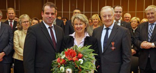 Bundesverdienstkreuzträger Wilhelm Hogrefe mit Ehefrau Renate und Landrat Peter Bohlmann vor Gästen bei seiner EhrungFoto: Bruns
