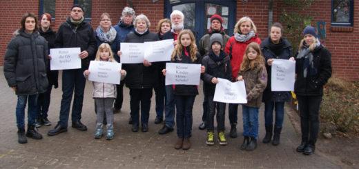 Kathrin Eilers (links) und Detlev Hansing (Achter von rechts) protestieren gemeinsam mit anderen Eltern, Kindern und Anwohnern gegen eine Schließung der Grundschule in Ströhe. Foto: Möller