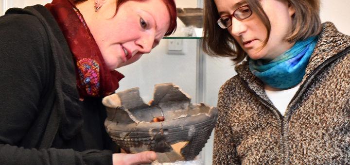 Ausgrabungsleiterin Saskia Behrens (links) und Wirtschaftsförderin Christa Linnemann begutachten ein verziertes Gefäß, eines der ärchaologischen Funde im Gewerbegebiet Ganderkesee-West. Foto: Konczak