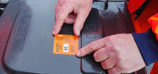 Hand klebt neue Gebührenmarke auf Mülltonnendeckel.