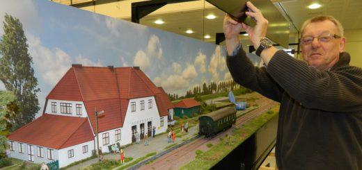 Seit Sonnabendvormittag steht in der Stadthalle der Aufbau für den Modellbahntag an. Mitorganisator Werner Windhorst zog am Nachbau des Worpsweder Bahnhofs die letzten Schrauben an. Foto: Bosse