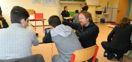 Der medienpädagogische Berater des Kreismedienzentrums, Karsten Machinek (rechts), unterstützt die Schüler bei der Arbeit am Tablet. Foto: Bosse