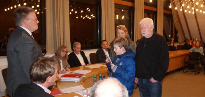 Der Schüler Mike Fettrau überreichte vor Sitzungsbeginn eine Liste mit 504 Unterschriften gegen die Schulschließung an Samgemeindebürgermeister Reinhard Kock. Foto: Möller