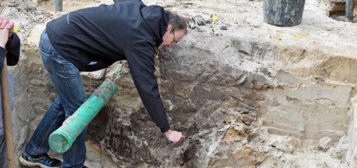 Archäologe Dr. Dieter Bischop kratzt in der Erde des alten Holzkastenbrunnens. Neben diesem Brunnen aus dem 5. Jahrhundert wurden auf dem Baufeld für das Übergangswohnheim für Flüchtlinge in Huchting (am alten Bolzplatz, Obervielander Straße) auch Brunnen gefunden, die noch 1.000 Jahre älter sind. Foto: WR