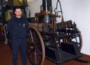 Jörn Gätjen posiert neben der historischen Dampfspritze in der Fahrzeughalle der Freiwilligen Feuerwehr Delmenhorst-Stadt. Foto: Garbas