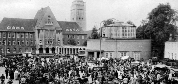 Der Marktplatz im Jahr 1927. Im Hintergrund sieht man das Rathaus und den Wasserturm, rechts im Bild die Markthalle samt Arkaden.Abbildung: Stadtarchiv Delmenhorst