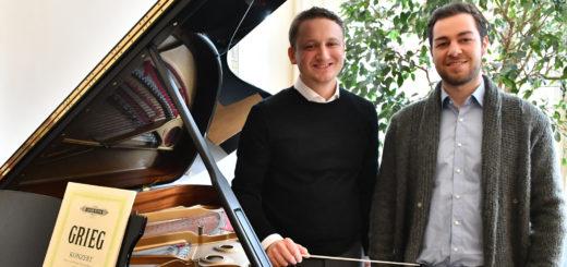 Adrian Rusnak und Joshua Krüger stehen am Flügel.