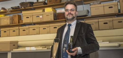Ins Stadtarchiv gehören alle Papiere, ins Museumsmagazin alle anderen Dinge. So wie die fast 100-jährige Bierflasche einer Delmenhorster Brauerei, die Christoph Brunken in seinem neuen Reich neben dem Wasserturm gefunden und nun dem Museum übergeben hat. Foto: Meyer