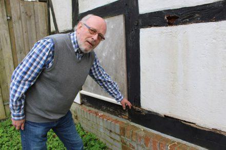 Klaus Peters, Vorsitzender des Trägervereins Burg Blomendal, zeigt die tiefen Risse im Fachwerk der Scheune. Foto: Harm