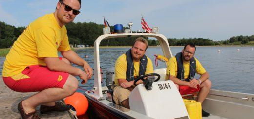 Philipp Postulka, Mirco Klein und Emre Ates (von links) sind drei der Ehrenamtlichen bei der DLRG, die am Sportparksee in Grambke kleine Wunden verarzten, mit dem Boot auf Streife unterwegs sind und auch mal Menschen aus dem Wasser retten. Foto: Harm