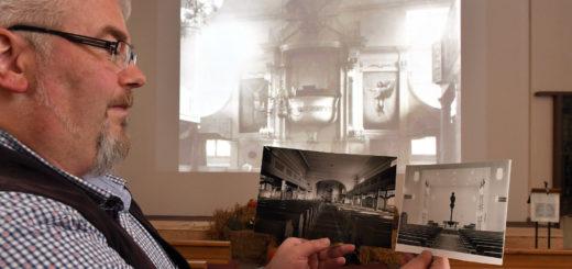Pfarrer Thomas Meyer präsentiert Aufnahmen des Altarraumes der Stadtkirche von 1789, 1908 und 1967.Foto: Konczak