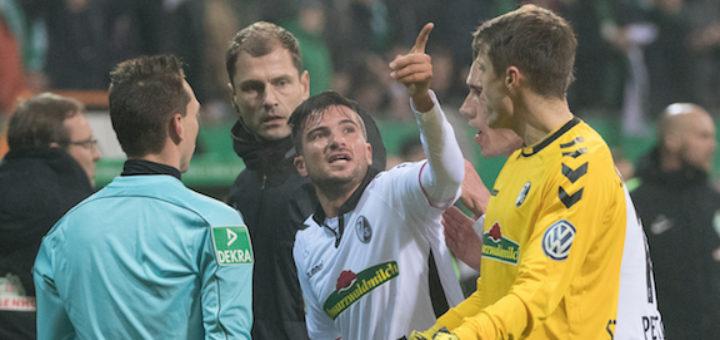 Freiburger Spieler diskutieren mit dem Schiedsrichter.