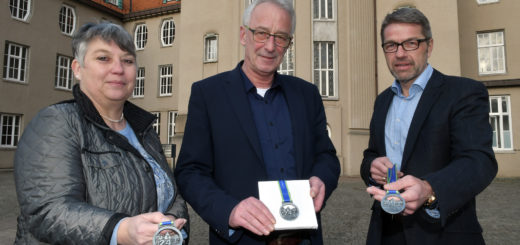 Birgit Woltjen-Ulbrich, Axel Jahnz und Dieter Meyer (v.l.) präsentieren die neuen Medaillen für den diesjährigen 24-Stunden-Lauf. Als Motiv haben die Verantwortlichen das Delmenhorster Rathaus gewählt.Foto: Konczak