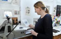 Julia Vogel begutachtet an der Druckerpresse das fertige Ergebnis. Foto: Konczak