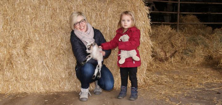 """Martina Warnken lässt die dreijährige Janna eine erst vor Tagen geborene Ziege streicheln. Der Huxfeld-Hof hat sich als """"KinderFerienLand""""-Betrieb zertifizieren lassen, die Bauernfamilie bereitet sich gerade auf die neue Saison vor. Foto: Möller"""