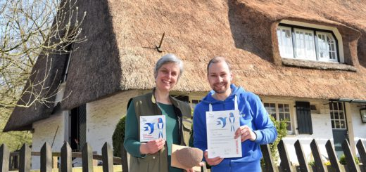 Florian Scheiba übergibt die Urkunde an Sarah Webb vor dem Wildhaus im Bürgerpark. Foto: Schlie