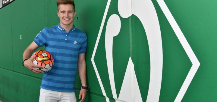 Johannes Eggestein lehnt an einer grünen Wand mit Werder-Raute.
