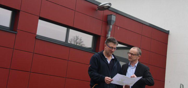 Geschäftsführer Guido Becker (r.) und Badleiter Oliver Wilms schauen sich die Pläne für die bevorstehende Erweiterung des Kursbereichs an. Das zweite Kursbecken wird auf dem Areal entstehen, das zurzeit als Betriebshof genutzt wird. Foto: nba