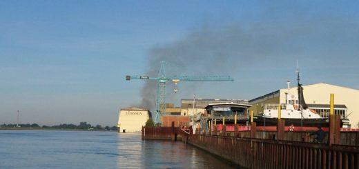 Auch am Freitagmorgen, Stunden nachdem das Feuer ausgebrochen ist, steht noch eine Rauchwolke über der Lürssen Werft. Foto: Harm