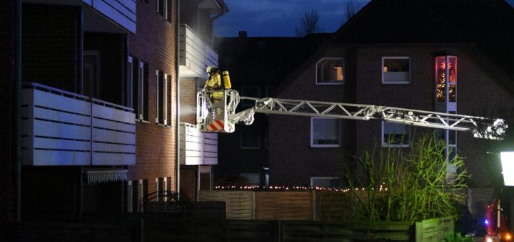Feuerwehrmann auf Drehleiter am Balkon des Mehrfamilienhauses.
