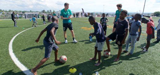 Für Werders Niklas Moisander (Mitte) und seine kickenden Kollegen war der Besuch eines Townships in Südafrika eine völlig neue Erfahrung. gumzmedia