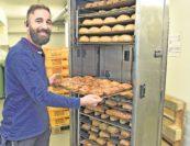 Abdul Mansour holt im Lager die frischen Brötchen aus dem Ofen. Der 26-Jährige ist seit sieben Jahren im Unternehmen und inzwischen stellvertretender Filialleiter.Fotos: Schlie