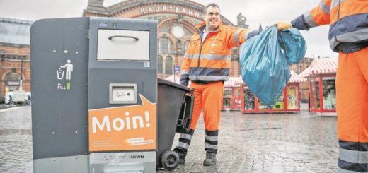 Mitarbeiter der Stadtreinigung mit dem neuen Abfallbehälter.