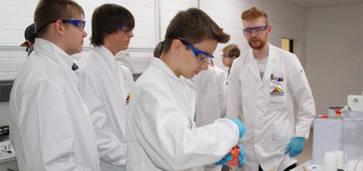 Thomas Wilkening (rechts) lässt die Schüler einen Härter in das Lackmaterial mischen, um ihnen zu demonstrieren, wie schnell Lack mittels einer chemischen Reaktion aushärten kann.Foto: Möller