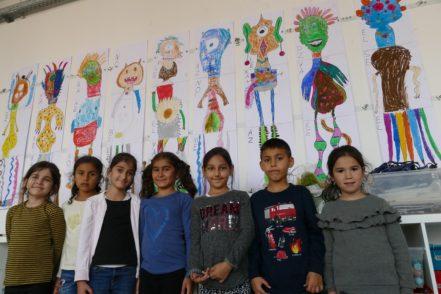 Einige der Kinder aus der Klecks-Gruppe vor ihren Bildern die sie zum Thema monströs gemalt haben. Foto: Bollmann