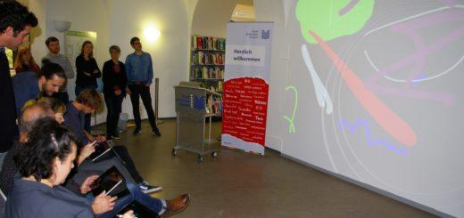 Erfolgreicher Test: Vor den Augen ihrer Kollegen probierten Mitarbeiter der Stadtbibliothek die Möglichkeiten der interaktiven Leinwand aus. Foto: Lürssen