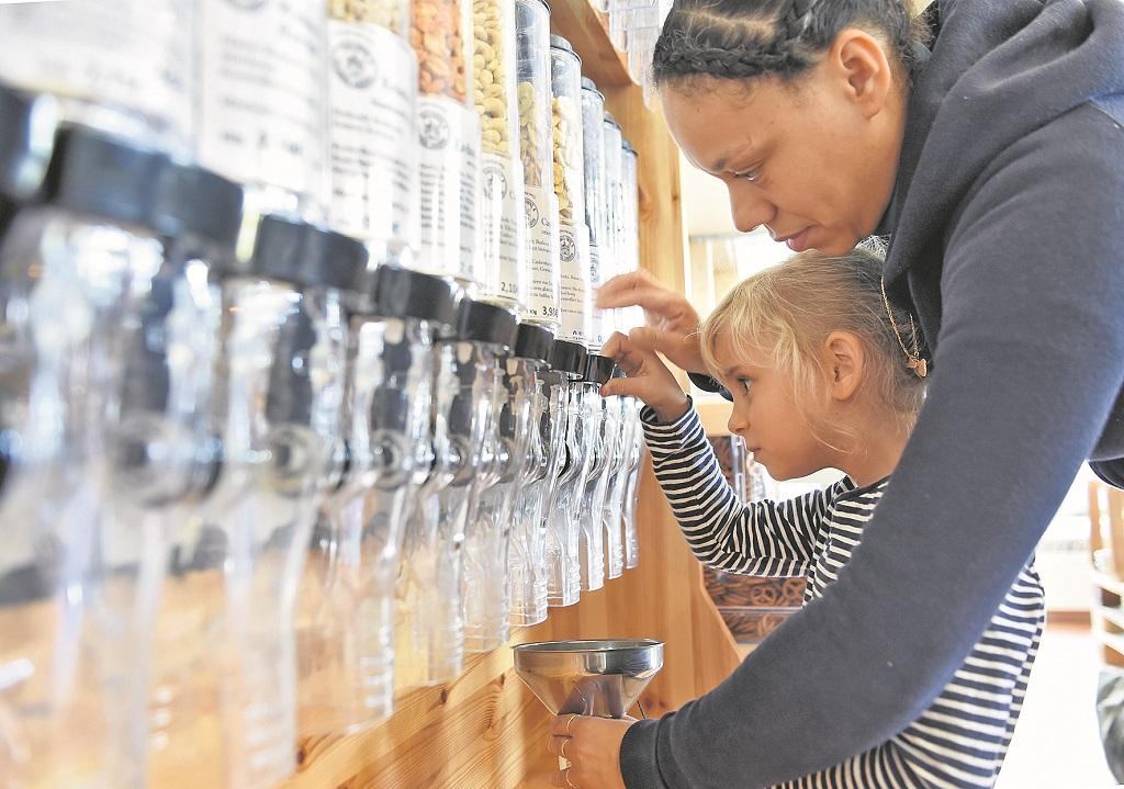 Das macht auch Kindern Spaß: In dem Unverpackt-Laden L' Epicerie Bio hilft Besitzerin Myriam Carneva der sechsjährigen Lina beim Abfüllen der Nüsse.Foto: Schlie