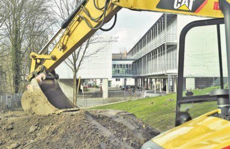 Das Gebäude links im Bild hinter der Baggerschaufel wird ausgebaut und nach Fertigstellung die gleiche Größe haben, wie Block D (rechts im Bild).Fotos: Schlie